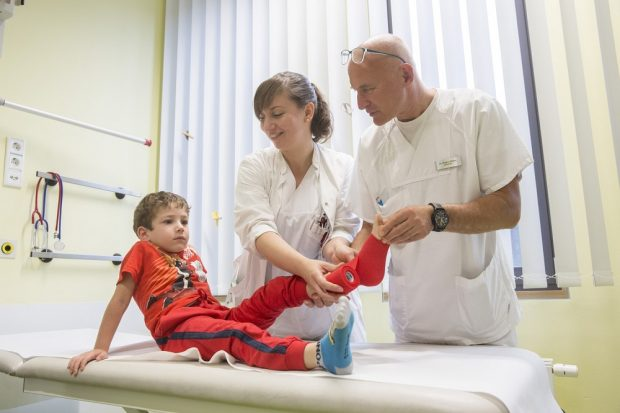 Auch den fünfjährigen Daniel hat es am linken Fuß erwischt. Bei Oberarzt Dr. Roland Böhm und Nicole Geuthel, Ärztin in Weiterbildung, von der Klinik und Poliklinik für Kinderchirurgie am UKL ist er in sehr guter Behandlung. Foto: Stefan Straube / UKL