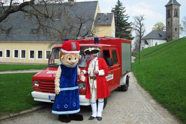 Löschi und Schließkapitän Clemens vor dem Löschfahrzeug der Festungsfeuerwehr. Foto: Festung Königstein gGmbH
