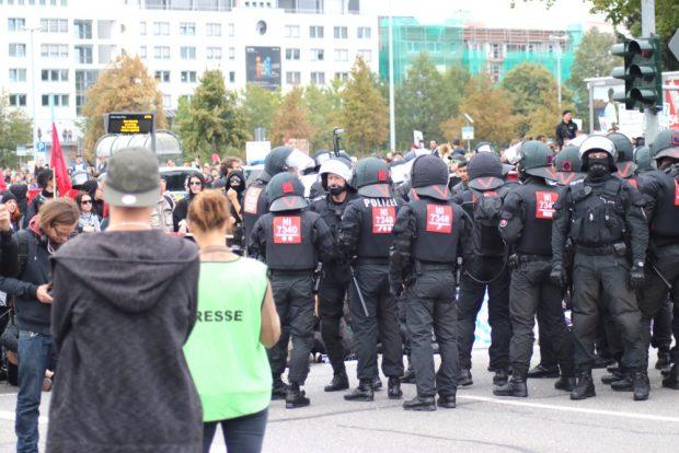 Angespannte Partystimmung. Die Polizei rückt zur Räumung vor. Dahinter unterhalten sich Menschen über ihre Stadt. Foto: Michael Freitag
