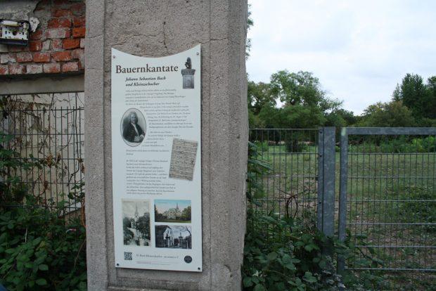 Die Tafel mit der Geschichte der Bauernkantate am Torweg neben dem Schösserhaus. Foto: Ralf Julke