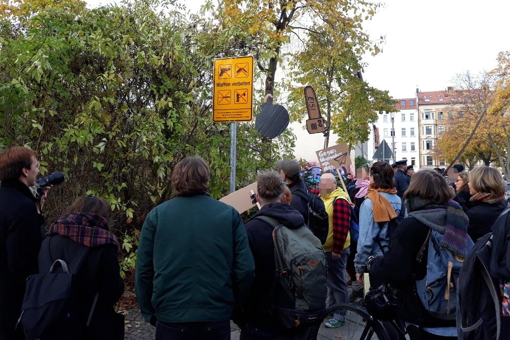 Mit Pappschildern bewaffnete Gegendemonstranten versammeln sich um das Verbotsschild. Foto: René Loch