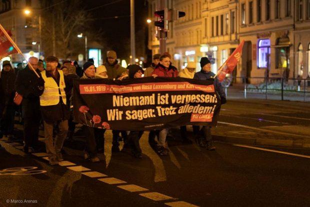 Volker Külow (l.) in gelber Weste und Marco Böhme (Linke, MdL, m.) hinter dem Transparent zum Gedenken an Rosa und Karl. Foto: Marco Arenas