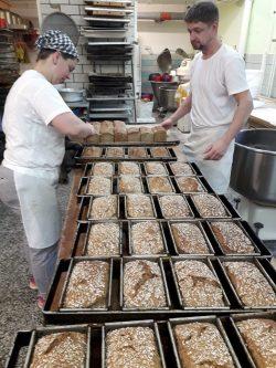 Frisch aus dem Ofen, Konditormeisterin Caroline Braune und Bäckergeselle Daniel Opitz beim Ausbacken von Dinkelvollkornbrot. Foto: Bäckerei Vogel