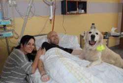Zusammen mit seiner Halterin Daniela Trambowsky (li.) besucht Therapiehund Sunny schwerkranke Patienten der Palliativstation des UKL auf ihren Zimmern und sorgt für Momente der Freude. Der Patient auf diesem Foto ist in der Zwischenzeit leider bereits verstorben. Foto: privat