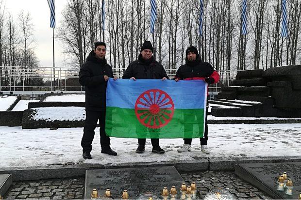 Richard Gauch (Mitte) zeigt mit zwei Begleitern die Flagge der Roma vor den ehemaligen Krematorien von Auschwitz-Birkenau. Foto: Ricky Burzlaff