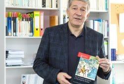 """Professor Matthias Middell mit dem von ihm herausgegebenen """"Routledge Handbook of Transregional Studies"""". Foto: Swen Reichhold/Universität Leipzig"""