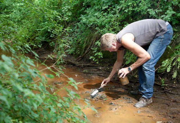 Dietmar Mieth nimmt aus einem Wassergraben in der Nähe der Anlage eine Sedimentprobe. Foto: Michael Billig