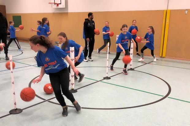 Dribbeln ist eine der Übungen bei der kinder+Sport Basketball Academy. Adika Peter-McNeilly hat es den Kindern zuvor erklärt. Foto: Kant-Gymnasium