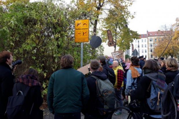 Gegendemonstranten bei der Einrichtung der Verbotszone vorm Verbotsschild. Foto: René Loch