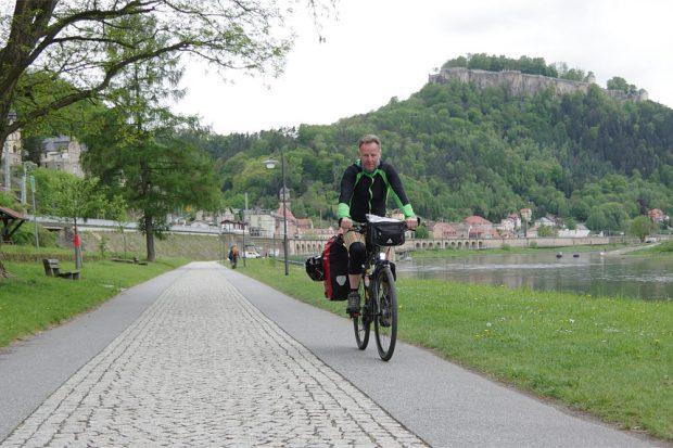 Oliver Pape am vierten Tag seiner Tour von Dessau bis zur tschechischen Grenze auf dem Elberadweg. Hier radelt der Berliner gerade durch das Städtchen Königstein in der Sächsischen Schweiz – im Hintergrund die berühmte Bergfestung. Foto: Hartmut Landgraf