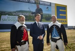 Ministerpräsident Michael Kretschmer (M.) steht mit den Kirchberger Bergbrüdern Wolfgang Prehl (l.) und Andre Prehl vor dem Megabanner. Quelle: Sächsische Staatskanzlei
