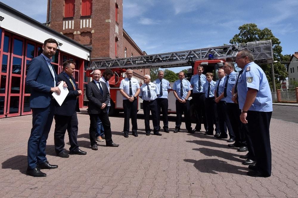 Vor der 25 Jahre alten Drehleiter der Schkeuditzer Feuerwehr übergibt Jens Kabisch (links) den mehr als eine halbe Million schweren Fördermittelbescheid. Foto: Landratsamt/Bley