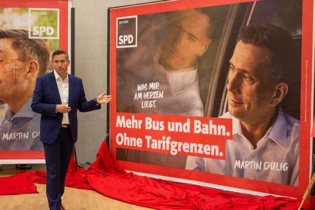 """Martin Dulig mit dem Plakat """"Mit Bus und Bahn. Ohne Tarifgrenzen"""". Foto: SPD Sachsen"""