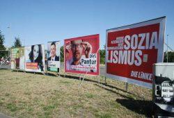 Einträchtig nebeneinander: Plakataufsteller am Wilhelm-Leuschner-Platz. Foto: Ralf Julke