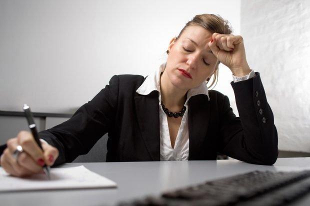 Müde Frau am Schreibtisch, Foto: BARMER