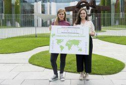 Rebecca Freitag und Pia Jorks mit dem internationalen Kampagnenschild. Foto: Change.org