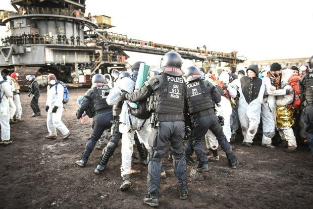 Rangeleien, mehr gab es nicht seitens der Polizei, welche selbst als erstes auf dem Bagger Stellung bezogen hat und diesen schützt. Foto: Tim Wagner