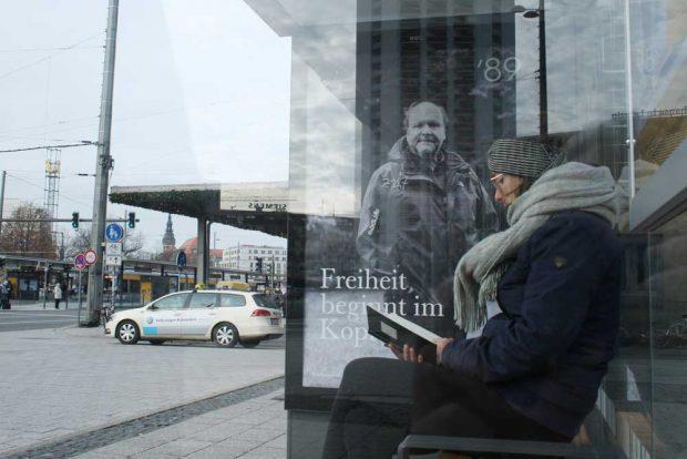 Leserin im Wartehäuschen mit Uwe-Schwabe-Motiv: Freiheit beginnt im Kopf. Foto: Ralf Julke