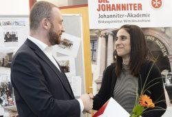 Lars Menzel überreicht Sozdar Mohammad ihr Zeugnis. Quelle: Johanniter/Sebastian Späthe