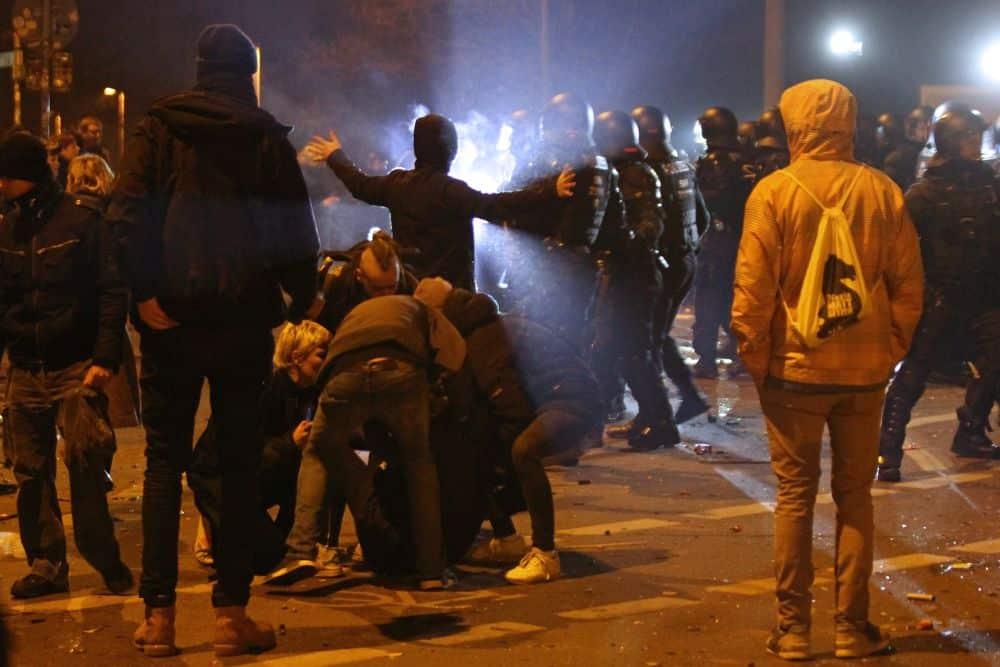 Versuche, die Beamten von einem am Boden liegenden Mann abzuhalten. Foto: Jan Kaefer