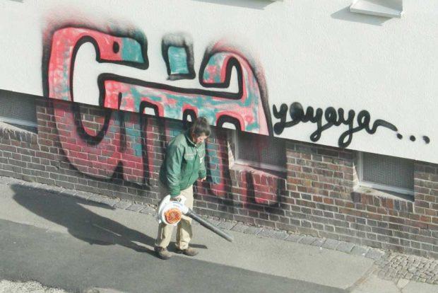 Connewitzer Graffiti und emsige Laubbläserin. Foto: Ralf Julke