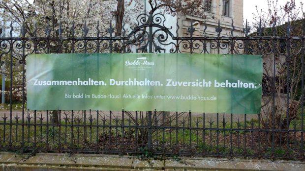 Das Banner am Zaun des Budde-Hauses. Foto: Budde-Haus