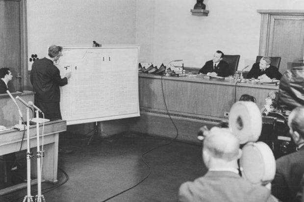 März 1966: Der vor dem Obersten DDR-Gericht angeklagte Auschwitzer Lagerarzt Horst Fischer zeigt an einer Tafel die Krematorien des Vernichtungslagers. Fischer wird im Juli 1966 hingerichtet. © Bundesarchiv