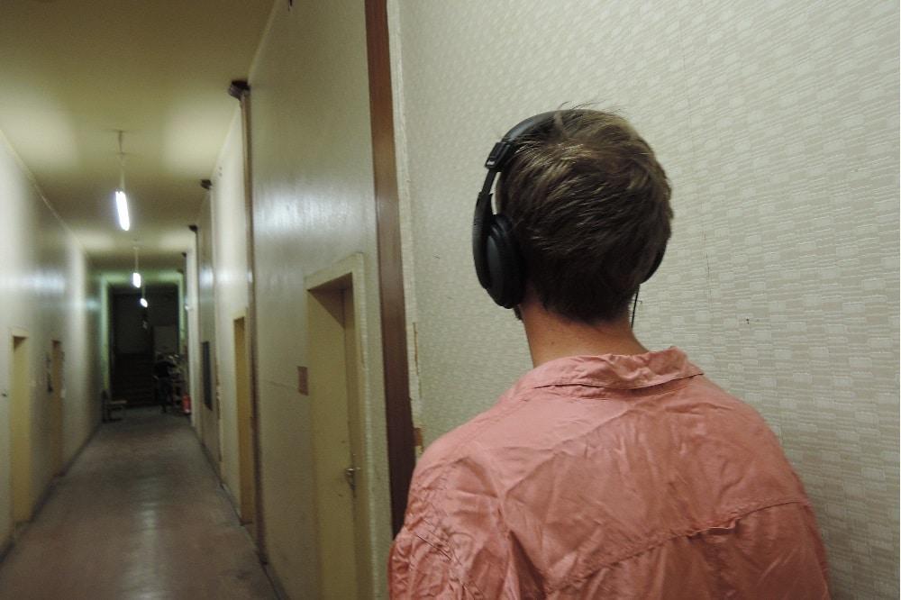 """Ein Besucher des Audiowalks """"Fabrik der Frauen"""" im Korridor der Halle 12, die damals die Betriebsschule der Spinnerei war. Foto: Diana Wesser"""