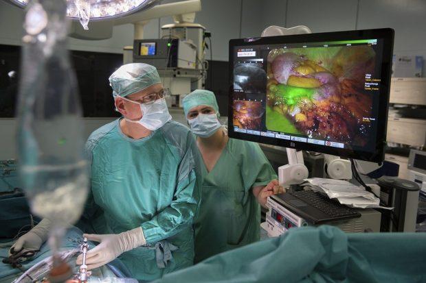 PD Dr. Boris Jansen-Winkeln, Oberarzt und Stellvertretender Leiter des Bereichs Viszeralchirurgie am UKL, bei einer Operation. Mit dem MIC-Turm, zu erkennen unterhalb des Bildschirms, können jetzt Robotik, Hyperspektral-Bildgebung und die Fluoreszenz-Darstellung mit Indocyanin-Green kombiniert werden. Foto: Stefan Straube / UKL