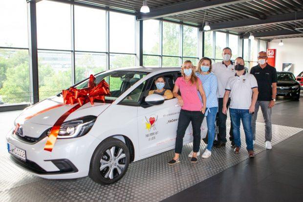 """Mobil zu sein ist für ihre Arbeit enorm wichtig: Katrin Mühler (3.v.l.), Leiterin des Nachsorgeteams, Koordinatorin Christin Henri-Dreßler (2.v.l.) und Julia Rothmann (li., im Auto) vom Nachsorgeteam freuen sich über das neue Fahrzeug aus den Händen von Sven Graser (3. V.r.), Vorsitzender des Vereins """"Paulis Momente hilft"""", seinem Stellvertreter Ingo Schulz (2.v.r.) sowie Robert Wagner (re.), Verkaufsleiter Honda Center Leipzig. Foto: Hagen Deichsel / UKL"""