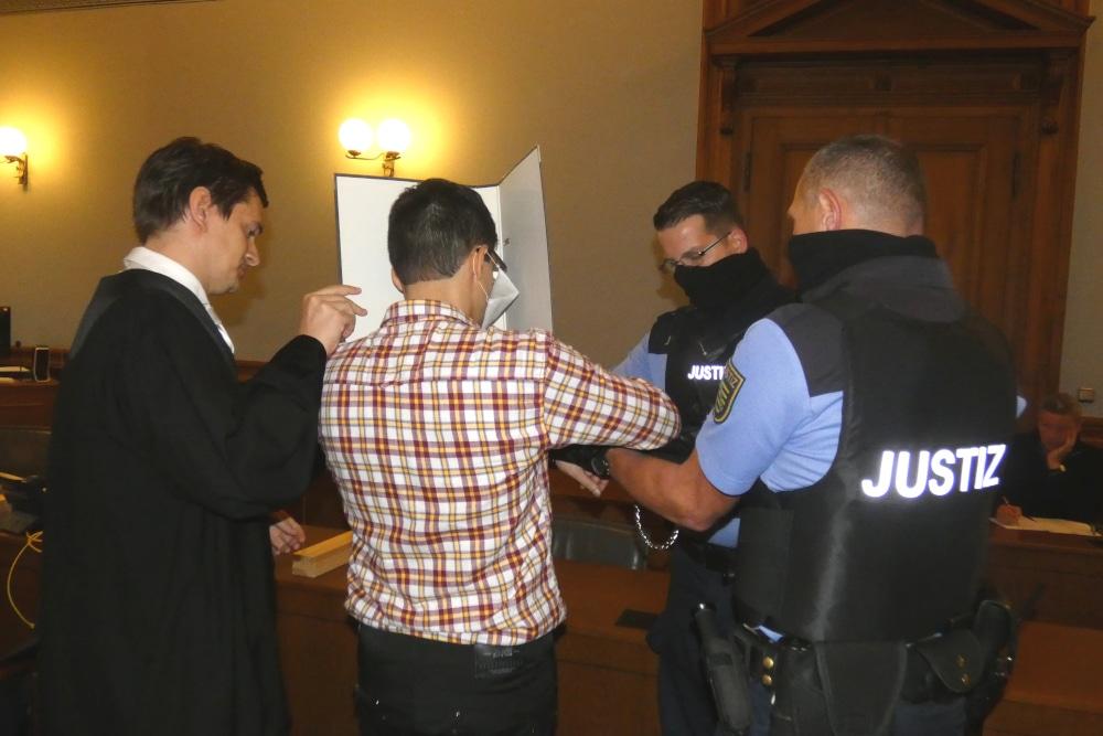 Justizbeamte nehmen dem Angeklagten Edris Z. (M.) zum Prozessbeginn am 7. Oktober die Handfesseln ab. Links sein Verteidiger Georg K. Rebentrost. Foto: Lucas Böhme
