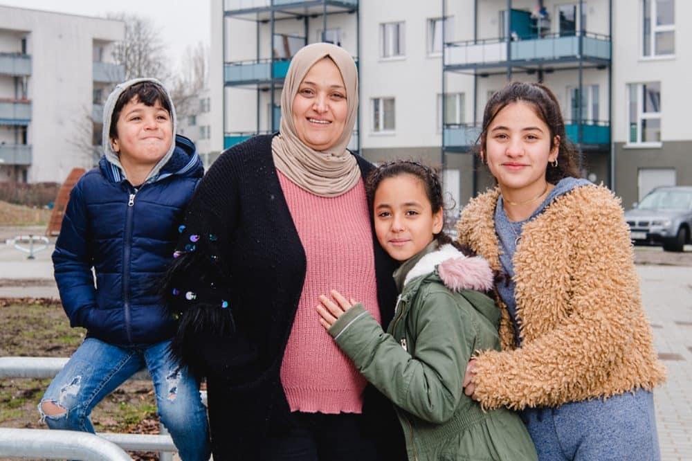 Halla Al-Saadi freut sich mit drei ihrer fünf Kinder über ihr neues Zuhause bei Vonovia. © Vonovia SE/Anika Dollmeyer