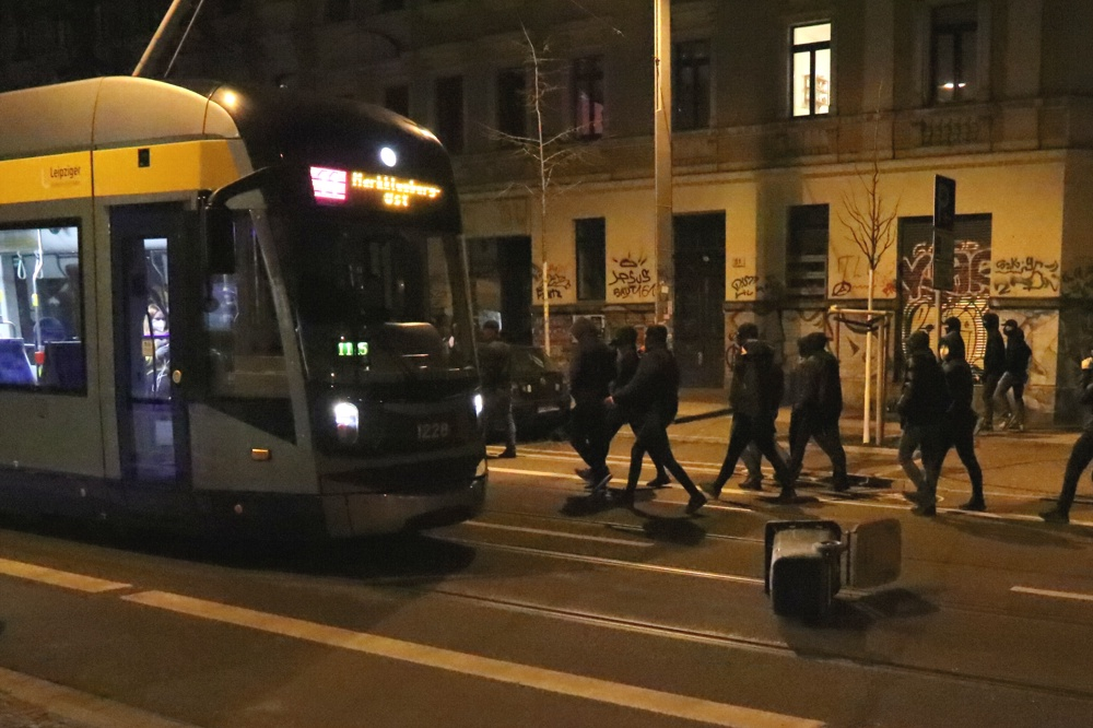 Anwohner protestieren, während eine Mülltonne und zwei Bauzäune auf die Straße gezogen werden. Foto: LZ