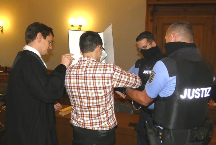 Edris Z. (31, M.) werden zum Prozessbeginn die Handfesseln abgenommen. Links sein Wahlverteidiger Georg K. Rebentrost. Foto: Lucas Böhme