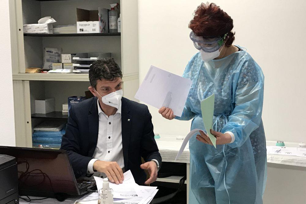 Bei der Auswertung eines positiven Tests bedarf es wegen der Quarantäne doch noch Papier. Landrat Henry Graichen und eine Mitarbeiterin aus dem Gesundheitsamt. Foto: Landkreis Leipzig