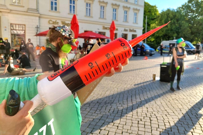 """Drohungen? Während der Gegenprotest mit großen Plastespritzen vor Ort wr, schürte die """"Bürgerbewegung"""" Angst vor dem Impfen. Foto: LZ"""