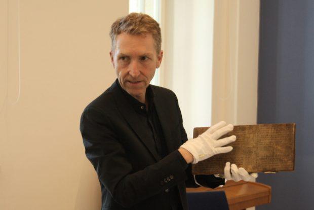 Dr. Christoph Mackert mit dem Leichenbuch aus dem Stadtarchiv. Foto: Ralf Julke